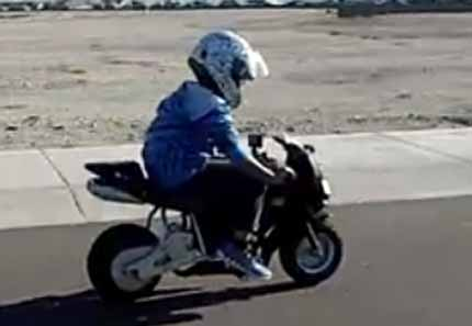 little boy having fun with his ride-on motorbike