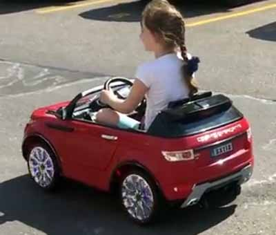 little girl enjoying her ride-on red car toy